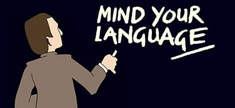 teacher writing on a blackboard the phrase mind your language